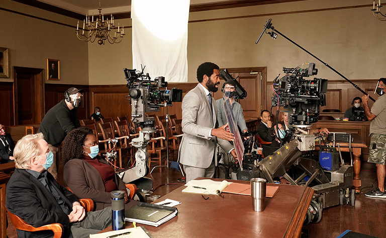 Multi-race actors including star Nicholas Pinnock in a courtroom scene with camera crew and boom operator in masks/face shields