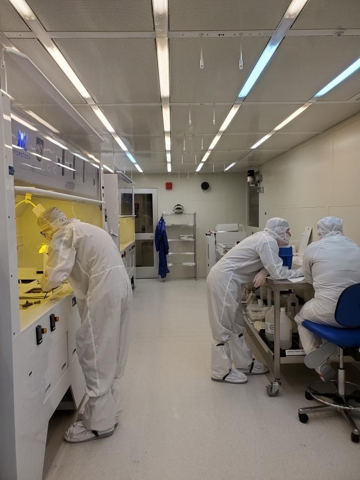 Employees in white personal protective equipment working inside a laboratory