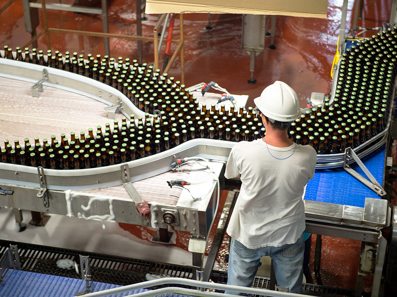 Factory worker overseeing conveyer belt of bottles for a product distributor