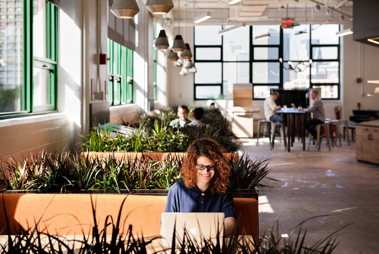 Woman working on laptop in Etsy headquarters.