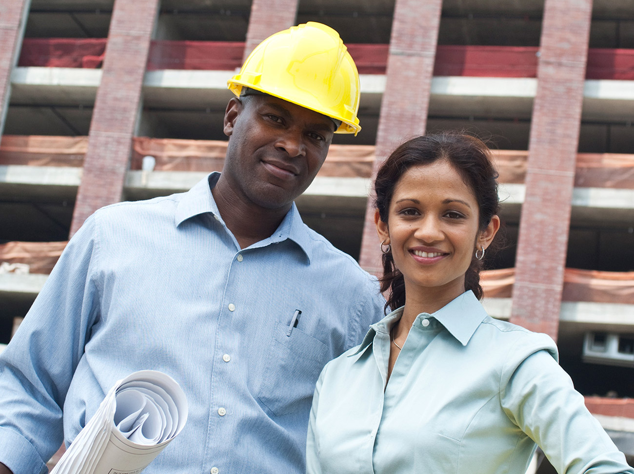 Man in hardhat and woman posed in front of a construction site