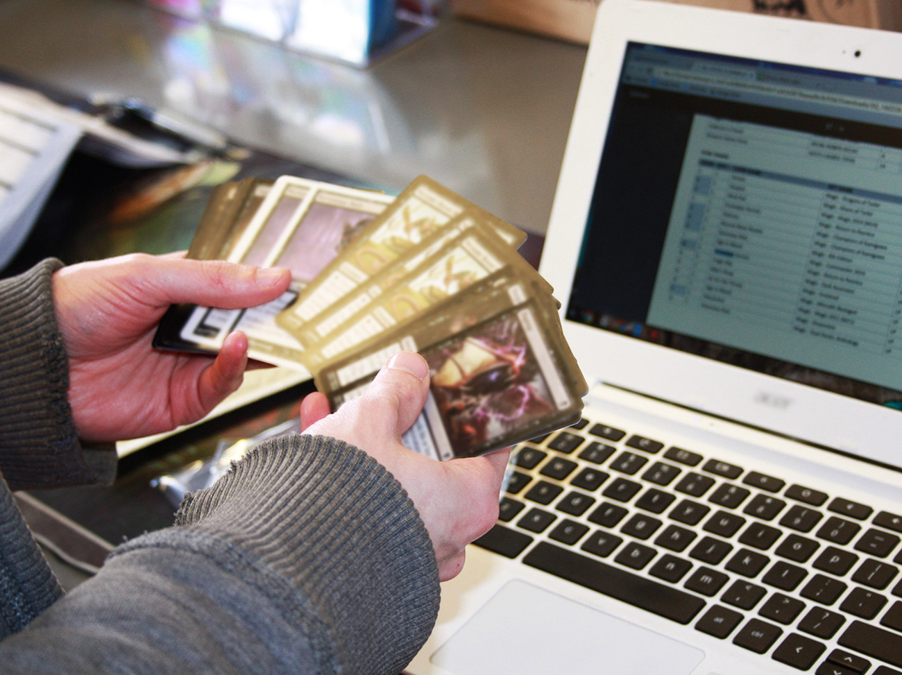 Hands holding playing cards in front of laptop with screen showing TCGplayer, an online marketplace focusing on collectible card gaming