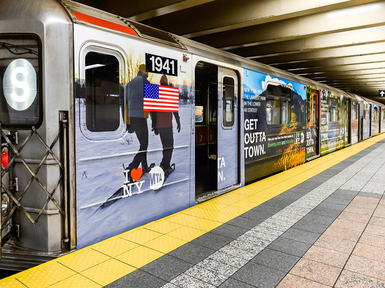 An MTA Subway train car wrapped in I Love New York decals