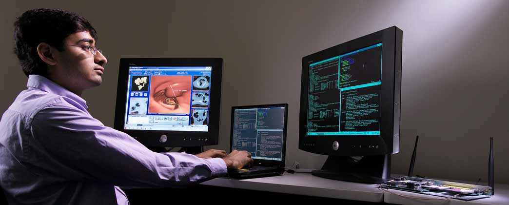 Worker in front of multiple computer monitors.