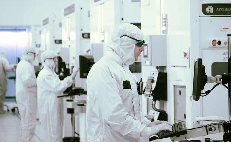 Applied Materials employees wearing clean suits working in a lab.